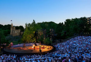 The Delacorte Theater at night with a view of Belvedere Castle in the background